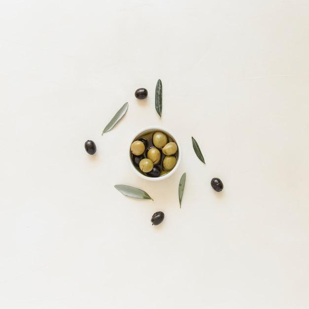 Tigela pequena com azeitonas e folhas Foto gratuita