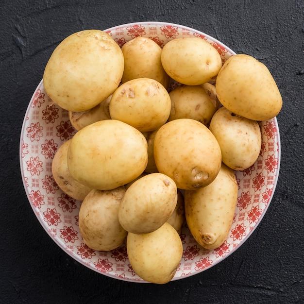 Tigela plana leiga com batatas Foto gratuita