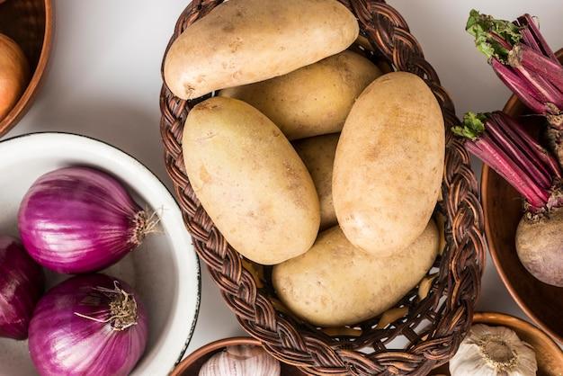 Tigela plana leiga e sacos com legumes Foto gratuita