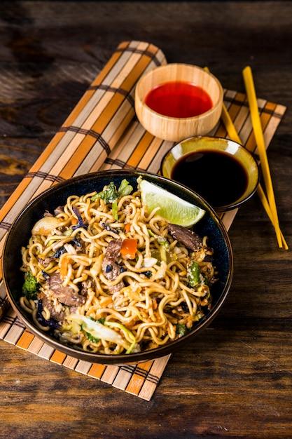 Tigela, udon, noodles, com, soja, e, pimentão vermelho, molhos, ligado, placemat, contra, escrivaninha madeira Foto gratuita