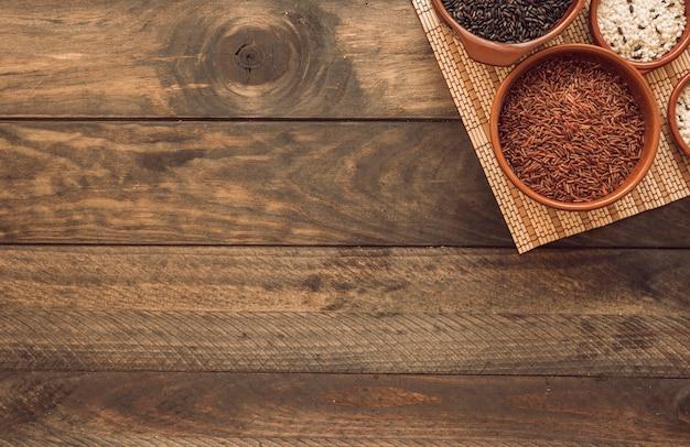 Tigelas de arroz crus diferentes no placemat sobre o fundo de madeira Foto gratuita