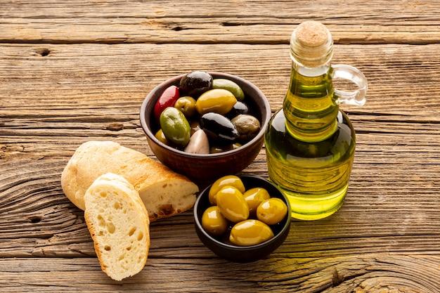 Tigelas de azeite de alto ângulo fatias de pão e frascos de óleo Foto gratuita