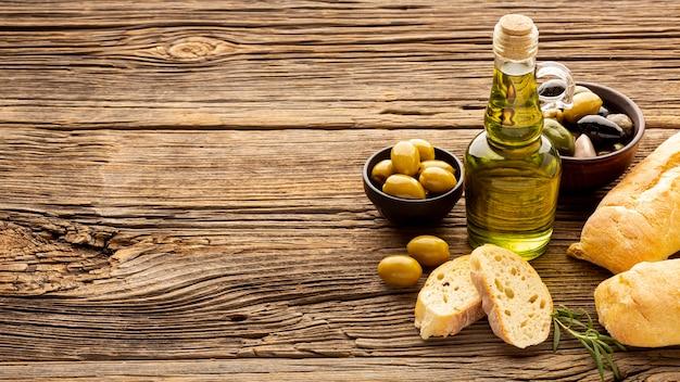 Tigelas de azeite de alto ângulo, fatias de pão e óleo botte com espaço de cópia Foto gratuita
