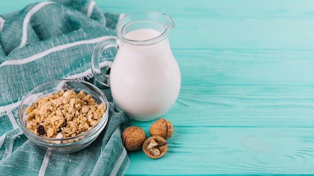Tigelas de cereais; jarra de leite e nozes na mesa de madeira verde com pano Foto gratuita