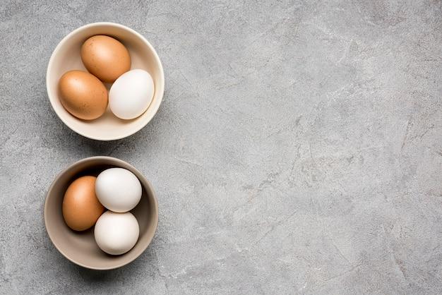 Tigelas de vista superior com ovos de galinha Foto gratuita