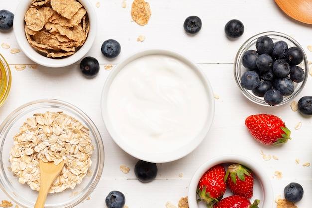 Tigelas planas de frutas e creme de leite Foto gratuita