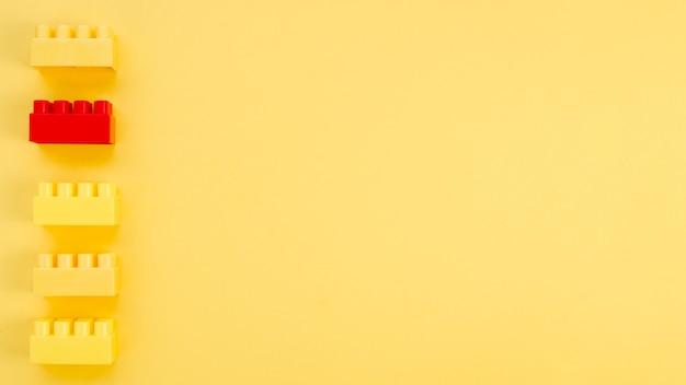 Tijolo de lego vermelho com amarelos e espaço de cópia Foto Premium