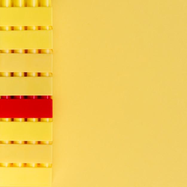 Tijolo de lego vermelho com tijolos de logotipo amarelo e espaço de cópia Foto gratuita