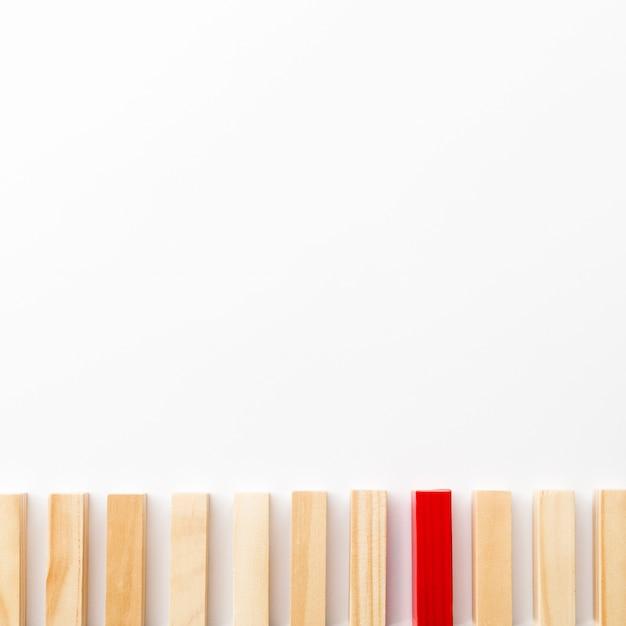 Tijolo de madeira vermelho, rodeado por normais, com espaço de cópia Foto gratuita