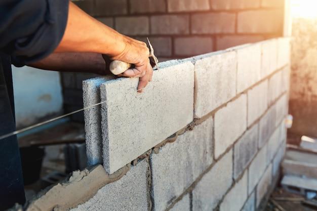 Tijolos de parede de construção de trabalhador com cimento Foto Premium