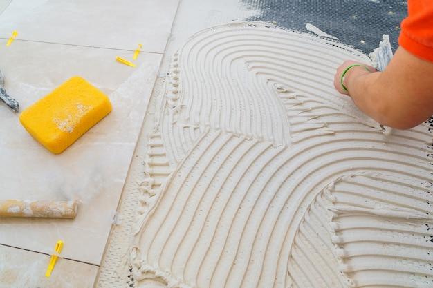 Tiler e gesso reparar o trabalho colocando a telha, colher de pedreiro em uma mão de homem Foto Premium