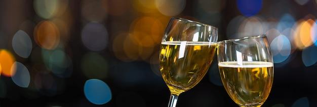 Tinindo com duas caneca de cerveja ou óculos sobre a foto desfocada da paisagem urbana para celebrar Foto Premium
