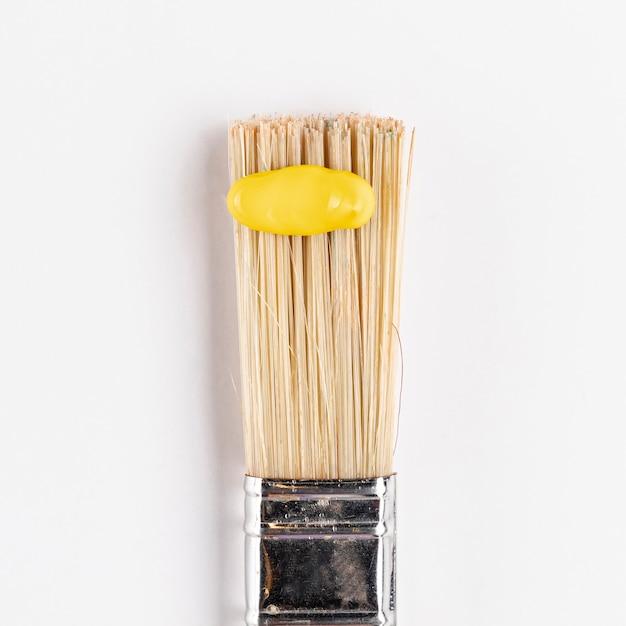 Tinta amarela na escova com fundo branco Foto gratuita