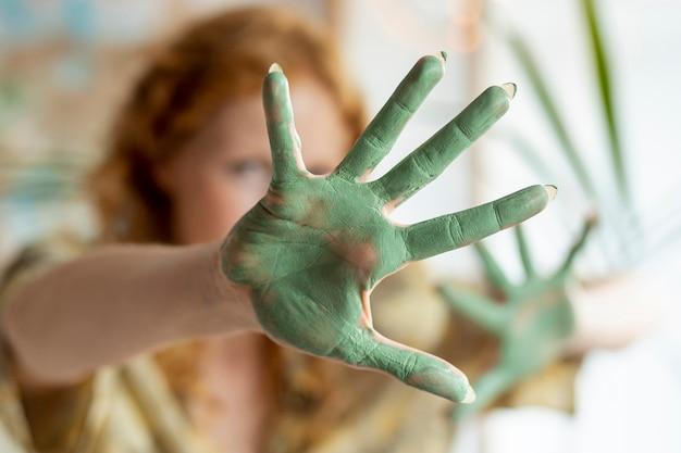 Tinta verde close-up na palma da mulher Foto gratuita