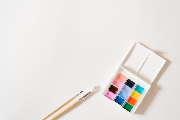 Tintas aquarela de cores diferentes nas valas em uma caixa branca e pincéis com alças de madeira sobre um fundo branco. copie o espaço. desenho e master classes para escola de arte Foto Premium