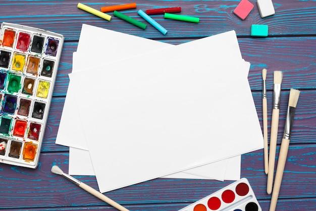 Tintas aquarela e bloco de notas em branco na mesa de madeira Foto Premium