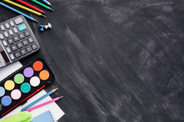Tintas coloridas, calculadora e lápis em fundo cinza Foto gratuita