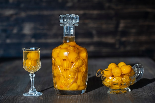 Tintura caseira de ameixa amarela em uma garrafa de cristal e um copo de cristal de vinho na mesa de madeira, ucrânia, close-up. conceito de bebidas alcoólicas de frutas vermelhas Foto Premium