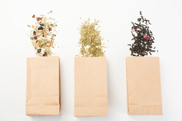 Tipo diferente de chá de ervas derramando do saco de papel marrom no fundo branco Foto gratuita