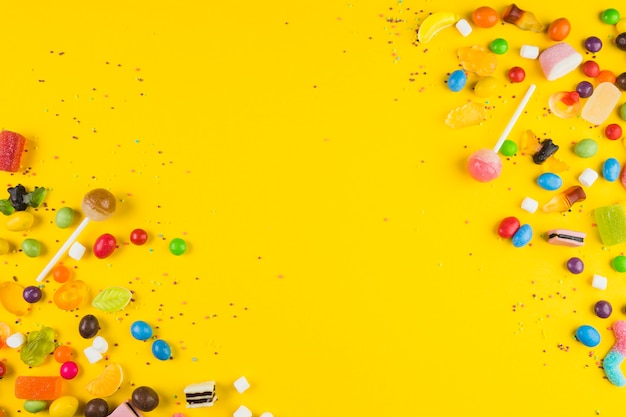 Tipo diferente de doces doces na superfície amarela Foto Premium