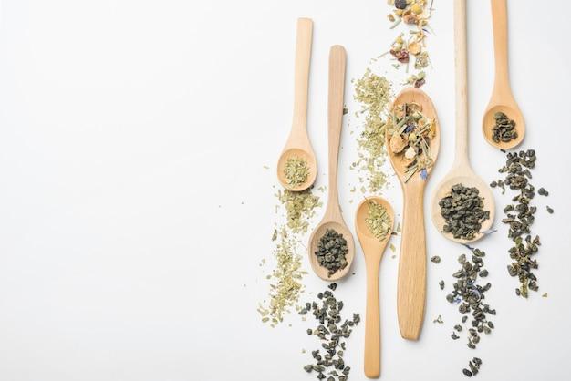 Tipo diferente de ervas na colher de pau contra o pano de fundo branco Foto gratuita
