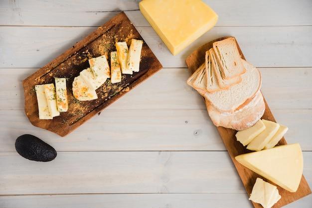Tipo diferente de fatias de queijo dispostas na bandeja de madeira com abacate sobre a mesa Foto gratuita