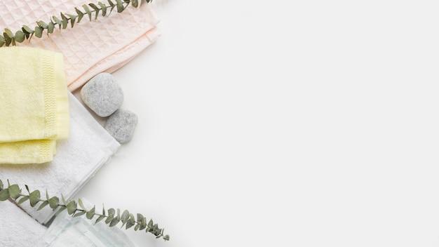 Tipo diferente de guardanapos dobrados com pedras dos termas e galhos no fundo branco Foto gratuita