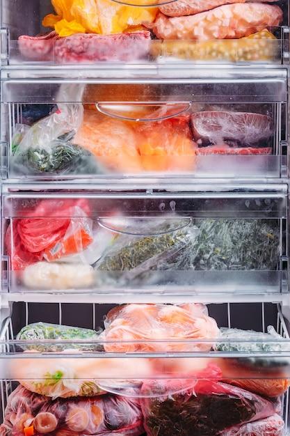Tipo diferente de legumes congelados em sacos de plástico em uma geladeira Foto Premium