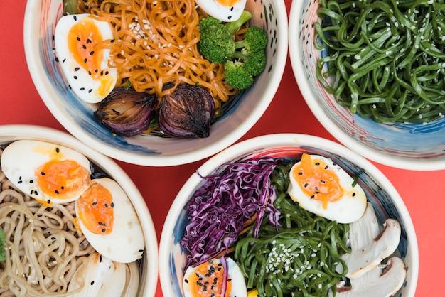 Tipo diferente de macarrão com ovos; algas e salada na tigela no pano de fundo vermelho Foto gratuita