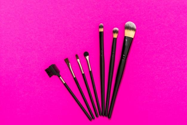 Tipo diferente de pincéis de maquiagem no fundo rosa Foto gratuita