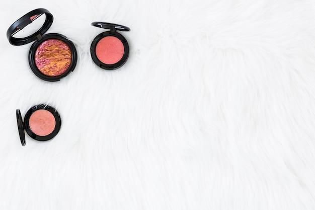 Tipo diferente de pó compacto rosa preto no pano de fundo de pele branca Foto gratuita
