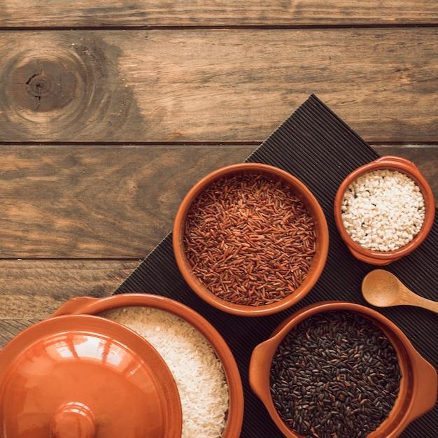 Tipo diferente de tigelas de grãos de arroz no placemat sobre a mesa de madeira Foto gratuita