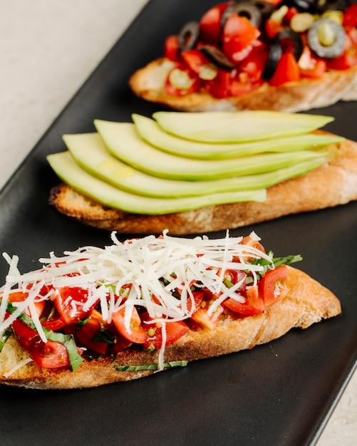 Tipos de árvore de sanduíches com tomate queijo maçã azeitona e outros ingredientes. Foto gratuita