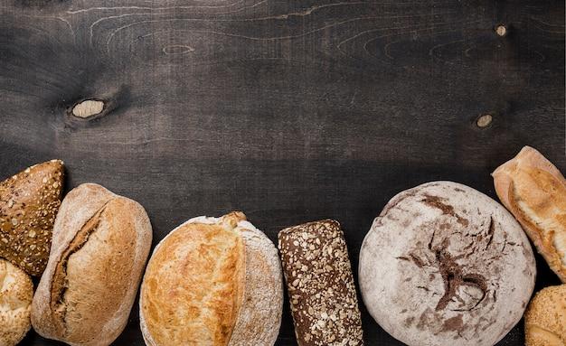 Tipos de lay plana de pão e cópia espaço preto fundo Foto gratuita