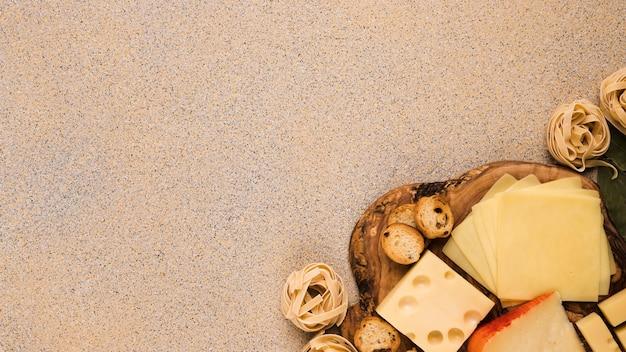 Tipos de queijos na montanha-russa de madeira com bolas de massa crua no canto da superfície texturizada Foto gratuita