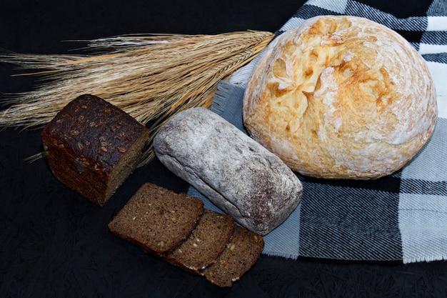 Tipos diferentes assorted do pão branco e preto em um fundo preto. Foto Premium