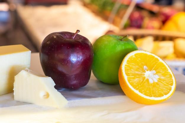 Tipos diferentes de queijo com frutas frescas na mesa Foto Premium