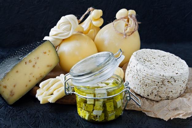 Tipos diferentes de queijo em um fundo preto. prato de queijos Foto Premium