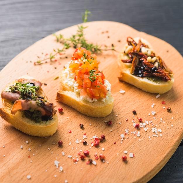Tipos diferentes de sanduíches coloridos na placa de desbastamento Foto gratuita