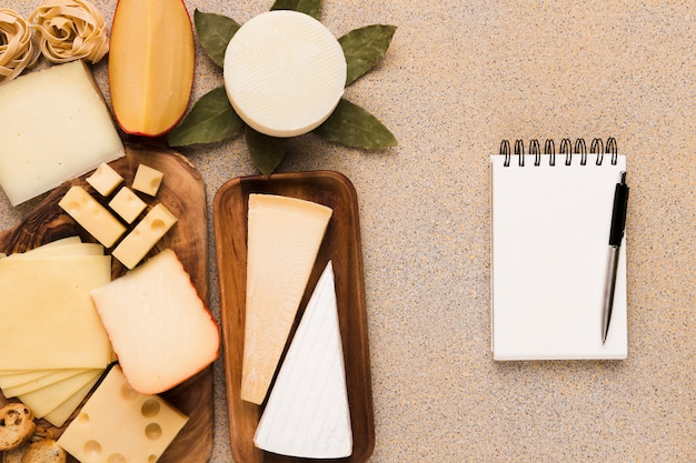 Tipos saudáveis de queijos na placa de madeira com o bloco de notas e a pena brancos em branco Foto gratuita