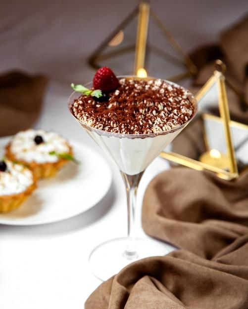 Tiramisu italiano em copo de coquetel coberto com granulado de café e morango Foto gratuita