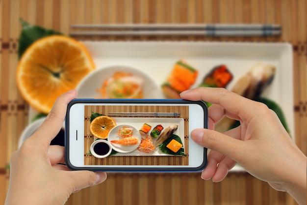 Tirar foto de sushi com smartphone Foto Premium
