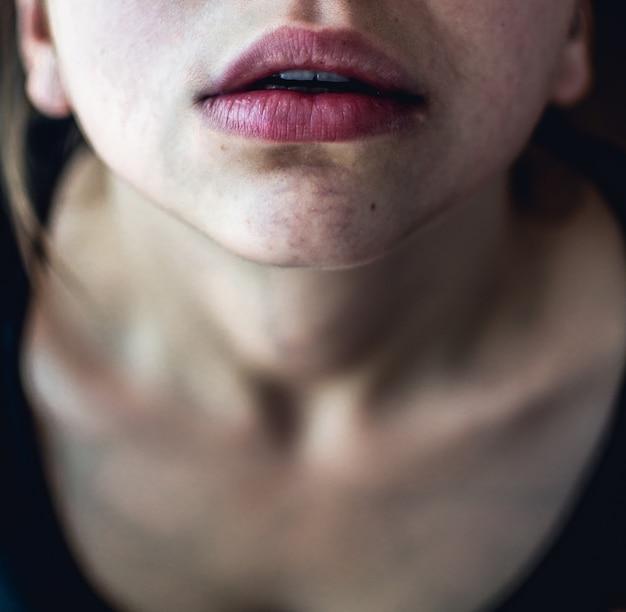 Tiro aéreo closeup seletivo de uma fêmea com pele pálida e lábios rosa secos, olhando para cima Foto gratuita
