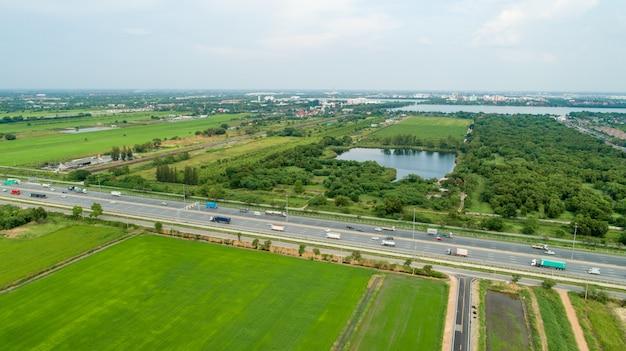 Tiro aéreo de carros dirigindo em um campo verde da estrada Foto Premium