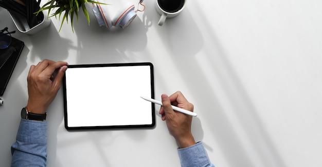Tiro aéreo de um designer gráfico com caneta stylus escrevendo na mesa gráfica com tela em branco. Foto Premium