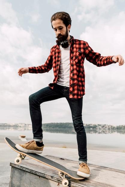 Tiro cheio, de, homem, equilibrar, ligado, skateboard Foto gratuita