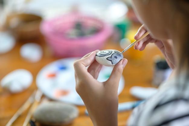 Tiro colhido da pintura do artista da moça com cor de água na rocha. Foto Premium