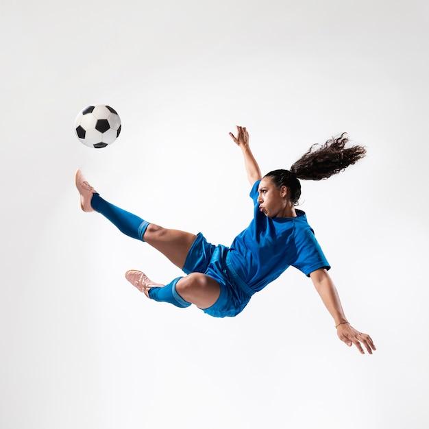 Tiro completo, ajuste, mulher, chutando bola Foto gratuita
