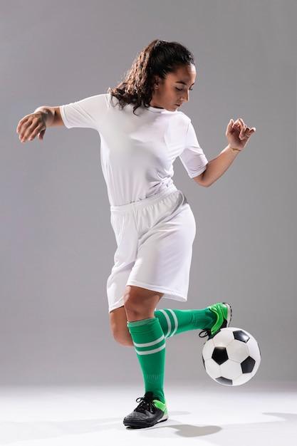 Tiro completo cabe mulher brincando com bola Foto gratuita
