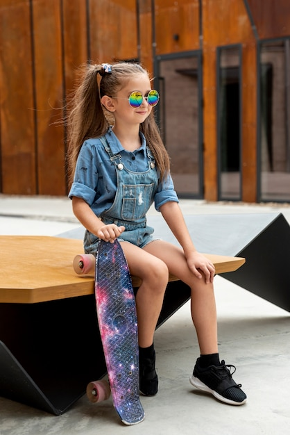Tiro completo de menina com macacão azul Foto gratuita